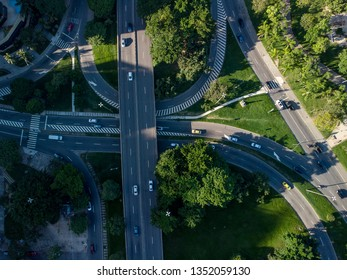 Highway crossroads in Rio de Janeiro seen from above. Aerial view of transit in green urban environment at sunrise.