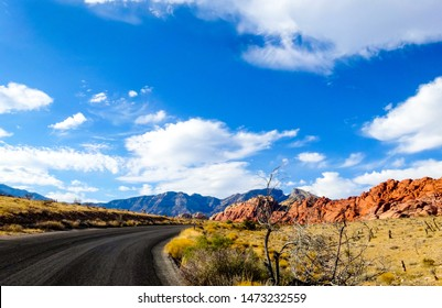 Highway curving past dramatic red and orange banded sandstone rock formations under a blue sky with white clouds in Nevada's Red Rock Canyon National Conservation Area, close to Las Vegas.