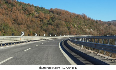 Highway E80 Roma-Pescara in province of L'Aquila, Abruzzo - the greenest region in Europe, central Italy during winter. The winding road goes through the hills and signs show abrupt turn to the right.