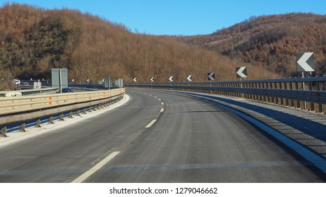 Highway E80 Roma-Pescara in province of L'Aquila, Abruzzo - the greenest region in Europe, central Italy during winter. The winding road goes through the hills and signs show abrupt turn to the left.