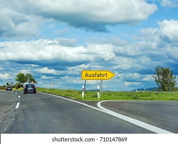 Highway exit raod sign (Ausfahrt), germany language - asphalt road with dramatic cloudy sky