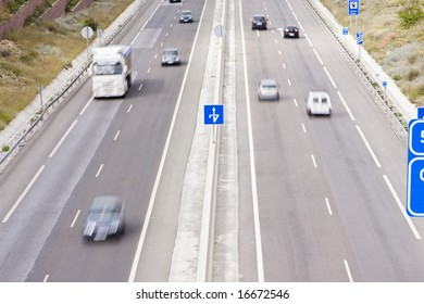 Highway full of blurred vehicles at high speed.