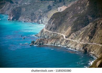 Highway hugs beautiful coastline for scenic drive on California coast between ocean and mountains