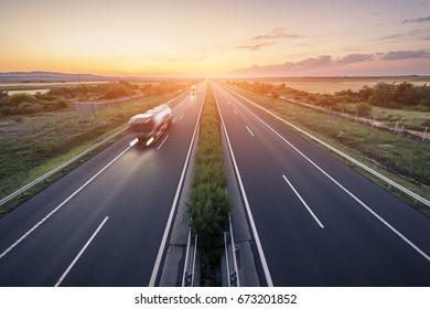 Highway landscape in a strong back light at sunset with motion blurred truck