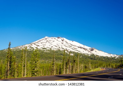A highway leading through a forest passing next to snowy Mount Bachelor near Bend, Oregon