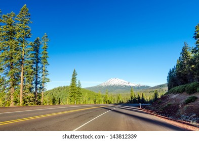 Highway leading through a lush green forest to Mt. Bachelor near Bend, Oregon