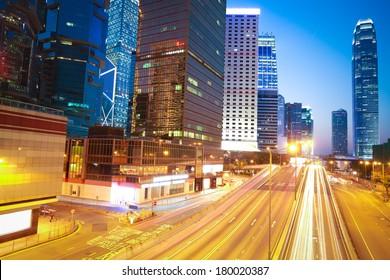 The highway light trails on the modern landmark buildings background in HongKong