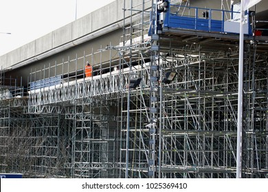 Highway maintenance. Scaffolding structure allowing workers to inspect and repair the underneath of a long concrete motorway flyover/bridge. An engineer checking a highway bridge from a gantry.