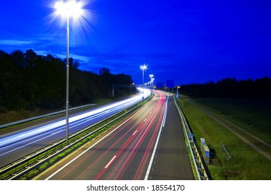 highway at night with rays of light passing by