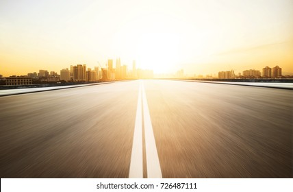 Highway overpass with modern city skyline background and evening sunlight