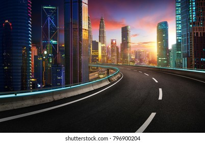 Highway overpass with modern city skyline and  skyscrapers at sunset.