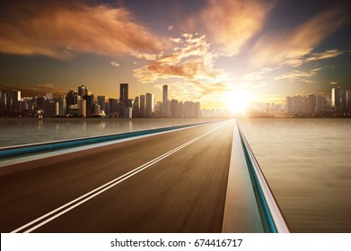Highway overpass motion blur with city skyline background . warm mood .