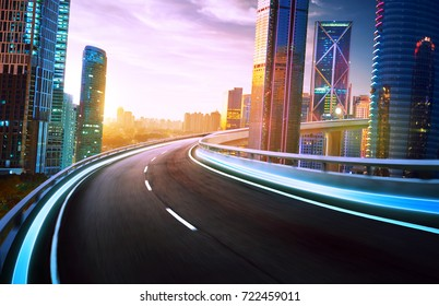 Highway overpass motion blur with city skyline and urban skyscrapers , sunset and twilight scene.
