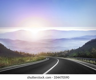 Highway road against mountains and a sky at the sunrise or sunset.