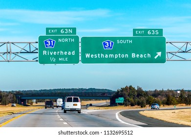 454ad8cddf Highway road sign to Hamptons New York in a blue sky day