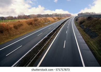 Highway runs through a rural landscape in northern Germany, also called german autobahn