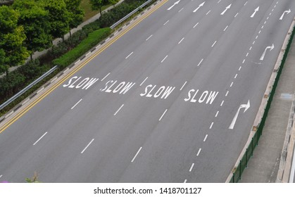 Highway seen from above with inscription on the ground: Slow, slow, slow, slow.