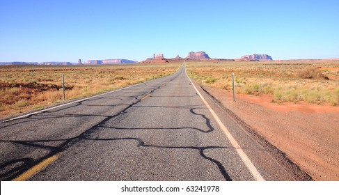 Highway stretches out in desert with rock formations of Monument Valley visible on the distant horizon