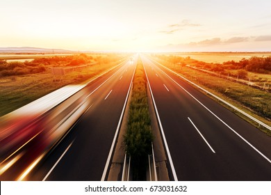 Highway in a strong back light at sunset with motion blurred truck landscape