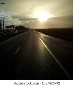 Highway in sunset, with raindrops out of focus on windshield. Taken out of moving vehicle, somewhere in the Netherlands