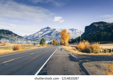 Highway surrounded by Fall colors and first snow in southwestern Colorado mountains, wolf creek pass