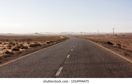 Highway through scenic desert of Jordan. High voltage powerlines along asphalt road in arid valley. Early morning in wilderness after sunrise. Electric power poles. Horizontal.