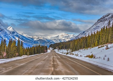 Highway through snow covered mountains in springtime