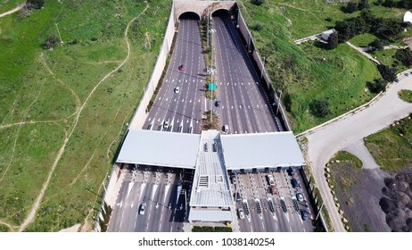 Highway traffic entering and exiting a Toll collection stop leading to a double tunnel surrounded by green landscape - Aerial image