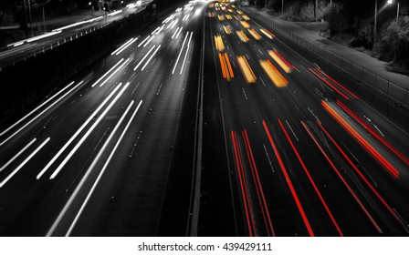 Highway Traffic at night with carlights passing by black and white composition with red tail lights