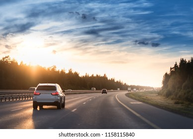 Highway traffic in sunset. Road with metal safety barrier or rail. cars on the asphalt under the cloudy sky.