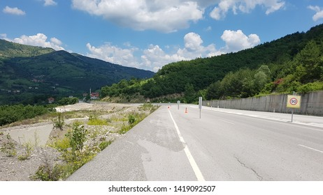 Highway in Turkey with  panorama of the horizon of mountains and small city (village) in sunny summer day. Asphalt road with beautiful scenic vivid nature view. Zonguldak Ankara Yolu. North of Turkey