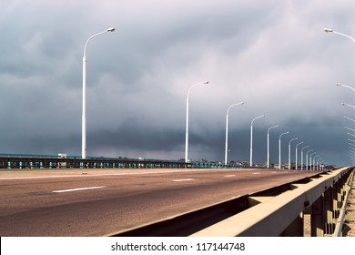 a highway under stormy clouds on the sky
