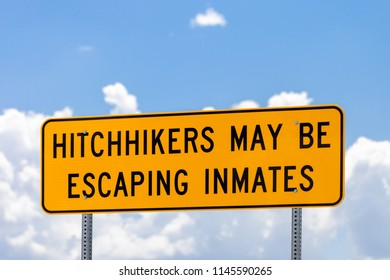 Highway warning sign about hitchhikers that might be escaping inmates