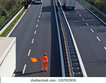 A highway worker with a high visibility work suit waves the orange flag to slow down trucks traffic before the roadblock