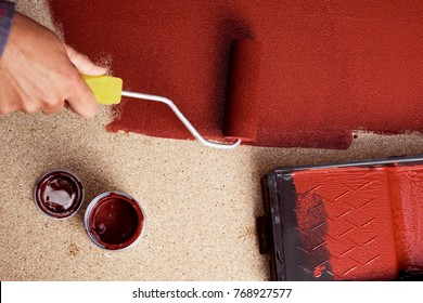 hihg-angle shot of a young caucasian man painting red a wooden board with a paint roller