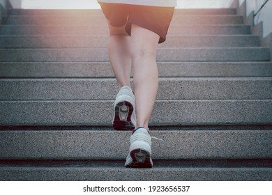 Hiit workout cardio running jogging up the stairs training. Staircase climbing run woman going run up steps. Runner athlete doing cardio sport workout.