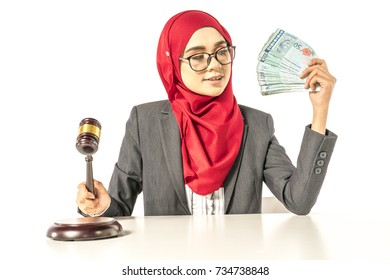 Hijab businesswoman looking money and holding gavel hammer. Financial concept.