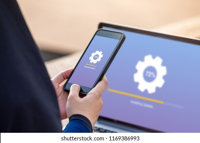 Hijab woman holding smartphone doing installing update process with gearbox percentage progress and loading bar with installing update on screen laptop background