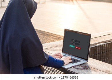 Hijab woman is working using laptop doing sign in membership username password on screen at outdoor
