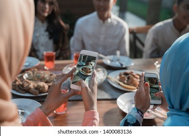 hijab women take photo of food dish while sitting on the house yard with friends together