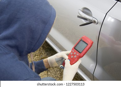 The hijacker tries to break into the car with a lock pick and a scanner.Code grabber . Car thief, car theft.