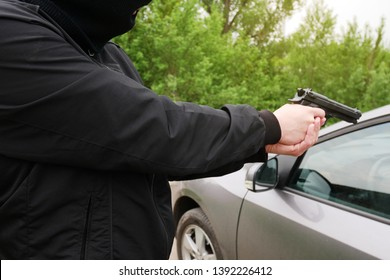 Hijacking a car. Threat of a pistol. Armed attack. A man in a black balaclava, a thief, a hijacker with a weapon in his hands.
