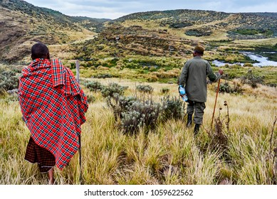 Hike in Olmoti Crater,  near Munge River  Ngorongoro Conservation Area Nationnal park Highlands with Masai Guide wearing traditionnal red blanket and Official ranger