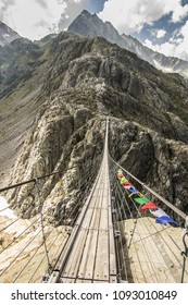 Hike in Swiss Alps with nature views; thin and long bridge connecting two mountains in Alps