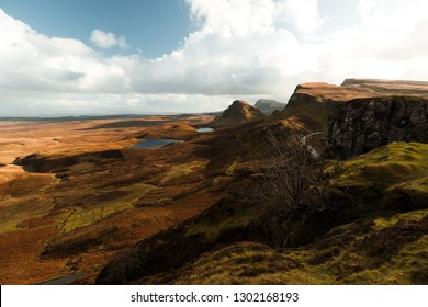Hike towards the famous dead tree at Quiraing on a sunny autumn day with cloudy blue sky and panorama view of Skye (Isle of Skye, Scotland, Europe)