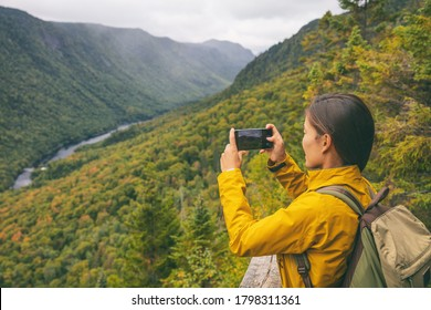 Hike woman hiker taking picture with phone of river view from top of trail hiking in Parc National de la Jacques Cartier, Quebec, Canada autumn travel camping lifestyle.