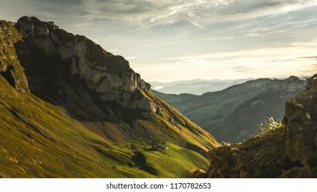 Hiker is alone on the rock summit. Wonderful daybreak in mountains in deep valley. The mountain of the Alpstein, Switzerland, Autumn 2017