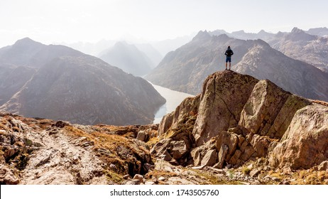 Hiker or alpinist at the top of a mountain. A success of mountaineer reaching the summit. Outdoor adventure sports alpine moutain landscape. Sunny day and a adventure man on a top of a peak.