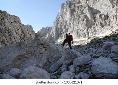 Hiker among amazing rock cliffs in the Prokletije mountains with a red backpack