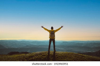 Hiker with arms up standing on the top of the mountain - Successful man enjoying triumph - Sport and success concept